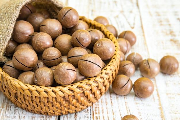 Nueces de macadamia descascadas y descascaradas en el fondo de madera del vintage