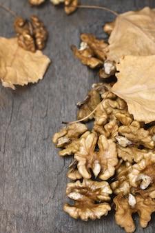 Nueces en madera oscura con hojas doradas.