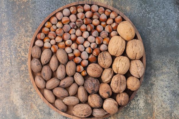 Nueces marrones mixtas nutritivas en cuenco de madera. foto de alta calidad