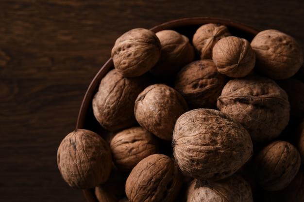 Nueces nueces en un recipiente sobre un fondo de madera marrón oscuro en una llave oscura