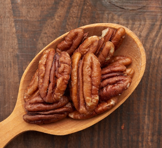Nueces peladas en una cuchara de madera marrón sobre un fondo de madera marrón, vista superior