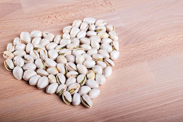 Nueces de pistacho formando una forma de corazón sobre fondo de piso de madera