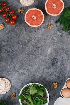 Nueces uvas uvas; pastel de arroz inflado espinacas; huevos y tomates cherry sobre fondo gris con textura