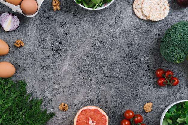 Nueces y verduras frescas sobre fondo gris concreto