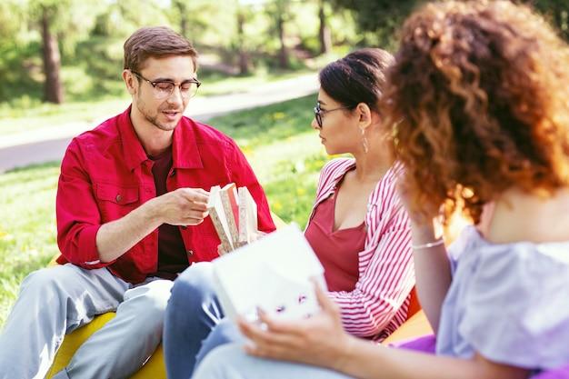 Nuestra determinación. atractivo hombre concentrado sentado al aire libre con sus compañeros de trabajo y discutiendo su proyecto