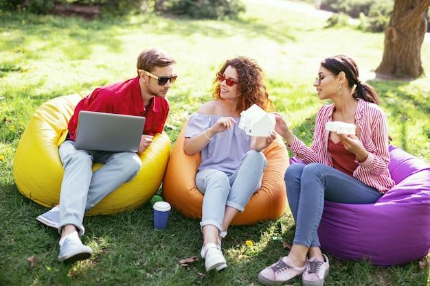 Nuestra startup. sonriendo colegas ambiciosos sentados al aire libre y trabajando en el proyecto