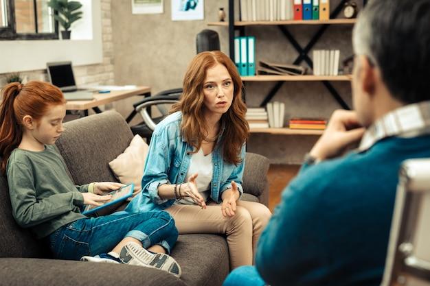 Nuestro problema. bonita mujer agradable mirando al psicólogo mientras le describe el problema.