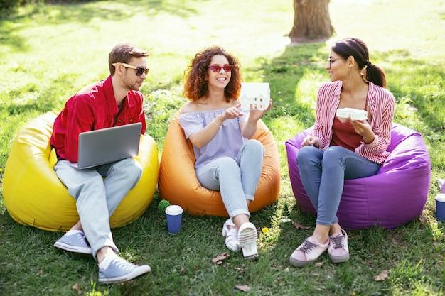 Nuestro proyecto de futuro. compañeros ambiciosos alegres sentados al aire libre y trabajando en el proyecto