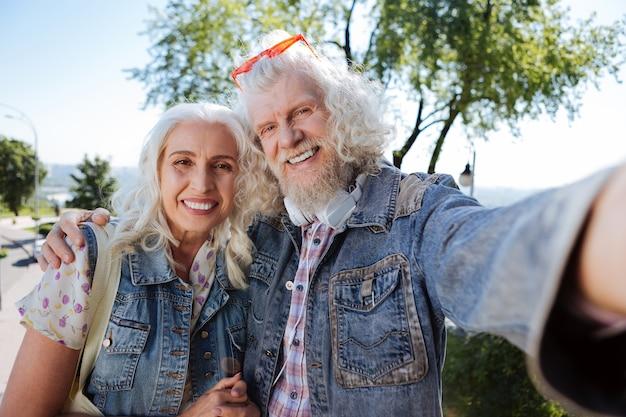 Nuestro selfie. agradable anciano sosteniendo una cámara mientras toma una foto con su esposa