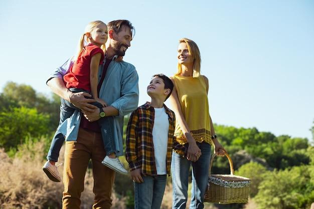 Nuestros niños. alegre hombre de pelo oscuro sosteniendo a su hija mientras pasa tiempo con su familia