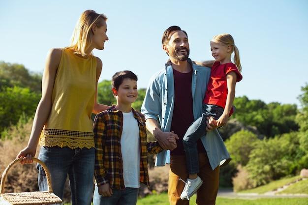 Nuestros queridos hijos. hombre de pelo oscuro alegre que sostiene a su hija mientras pasa tiempo con su familia