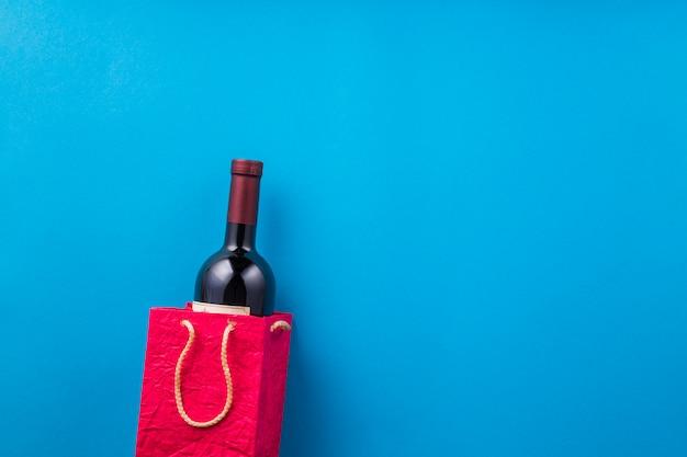 Nueva botella de vino en bolsa de papel roja contra el fondo azul