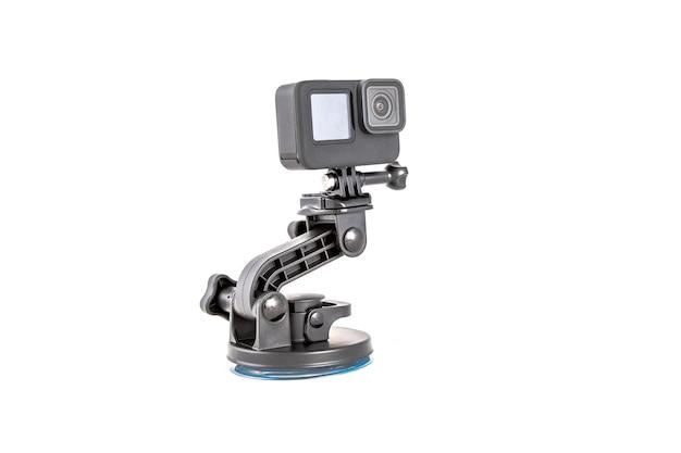 Nueva cámara de acción de color negro sobre trípode de montaje aislado sobre fondo blanco.