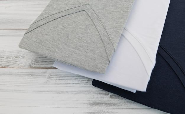 Nueva camisa negra, blanca y gris con cuello en v sobre fondo blanco de madera