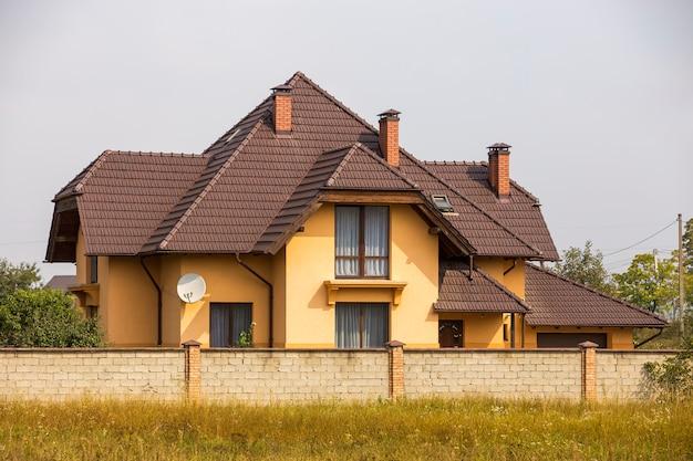 Nueva y confortable cabaña de dos pisos con empinado techo de tejas, antena parabólica en la pared de estuco,
