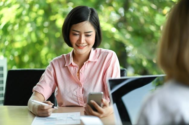 Nueva empresaria sentado en la oficina usando un teléfono móvil y sonriendo, sus colegas están usando una computadora portátil sentada enfrente.