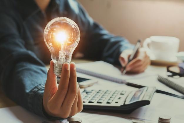Nueva idea y concepto creativo para la mano de la mujer de negocios que sostiene la bombilla en la oficina