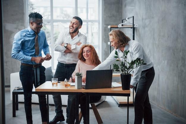 Nueva idea loca. equipo de negocios jóvenes trabajando en un proyecto con un portátil en la mesa y sonriendo