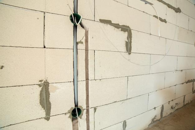 Nueva instalación de cableado eléctrico, cajas plásticas y cables eléctricos para futuras tomas de pared, concepto de renovación.