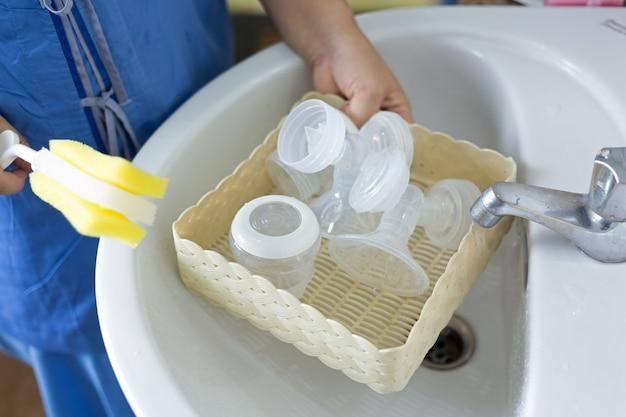Nueva madre lavando el extractor de leche automático.