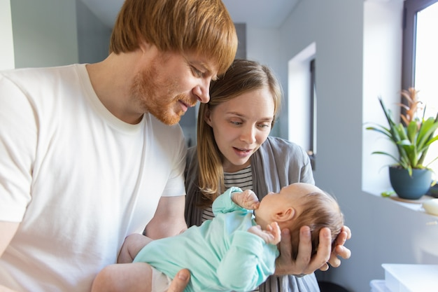Nueva madre y padre sosteniendo y abrazando al bebé