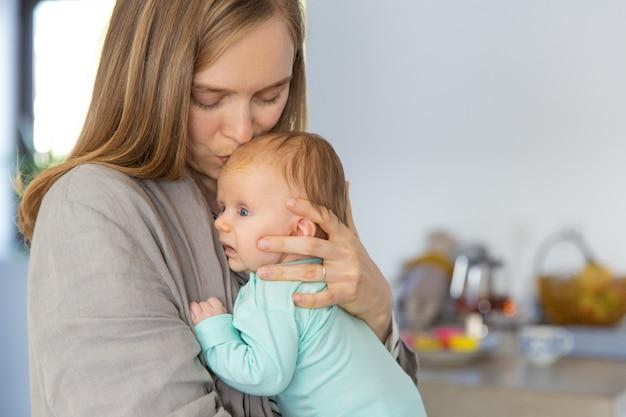 Nueva mamá abrazando y besando bebé