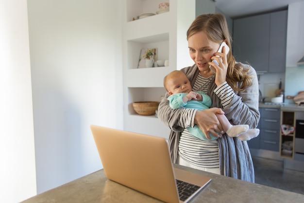 Nueva mamá enfocada que detiene al bebé