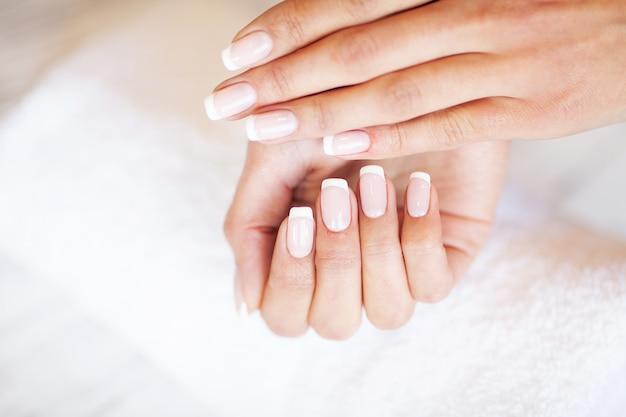 Nueva manicura. vista lateral del proceso de manicura en el salón. el manicurista profesional brinda un servicio al cliente.
