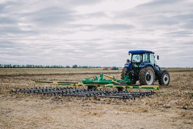 Nueva maquinaria agrícola, tractores en movimiento en el campo de demostración en la exposición agro