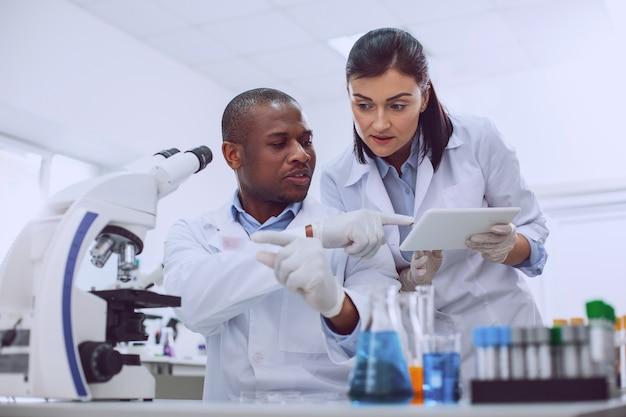 Nueva prueba. investigador calificado concentrado vistiendo un uniforme y haciendo una prueba
