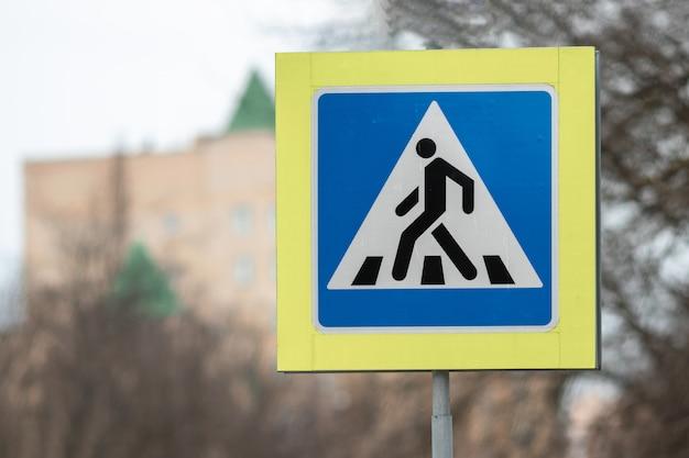 Nueva señal de tráfico del paso de peatones en el cielo azul.