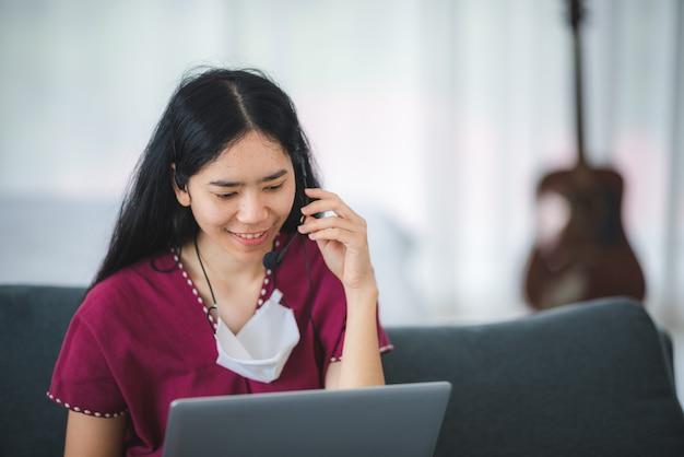 Nueva tendencia normal de agente de servicio al cliente femenino en el centro de llamadas que trabaja durante la cuarentena en casa con una computadora portátil y un teléfono principal