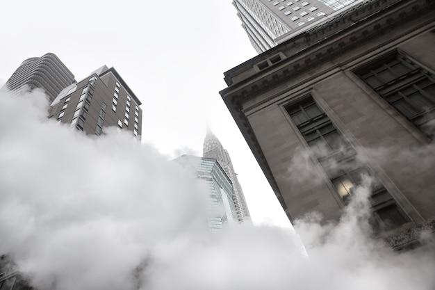 Nueva york, estados unidos - 03 de mayo de 2016: empire state building. escena de una calle de manhattan. nube de vapor del metro en las calles de manhattan en nueva york. vista típica de manhattan