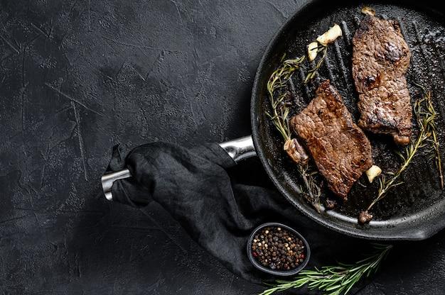 Nueva york filete en una sartén. carne a la parrilla. vista superior.