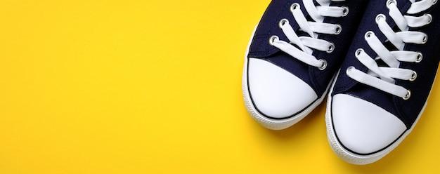 Nuevas y limpias zapatillas deportivas azules con cordones blancos, sobre un fondo amarillo brillante. bandera.