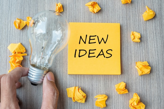 Nuevas palabras de la idea en una nota amarilla y papel desmenuzado con el empresario