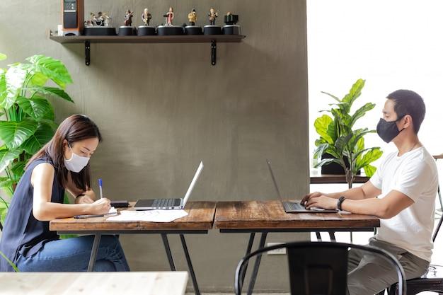 Nuevas personas normales de coworking que trabajan dentro con una máscara protectora para la propagación del coronavirus