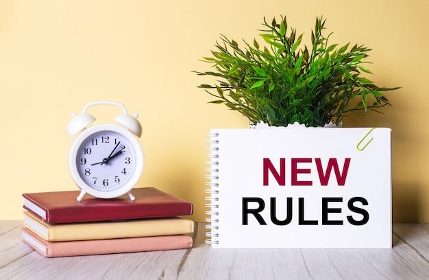 Nuevas reglas está escrito en un cuaderno junto a una planta verde y un despertador blanco, que se encuentra en diarios coloridos.