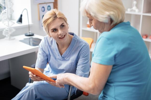 Nuevas tecnologías. agradable mujer de edad apuntando a la pantalla de la tableta mientras está sentada con su enfermera