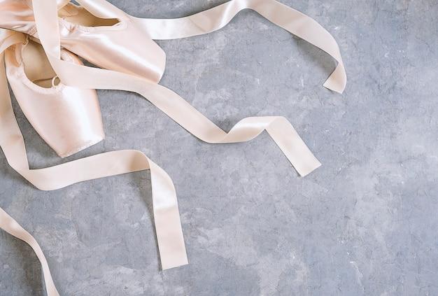 Nuevas zapatillas de punta de ballet rosa sobre fondo gris