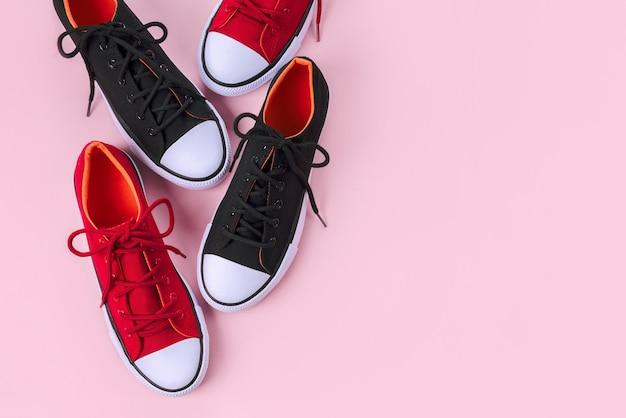 Nuevas zapatillas rojas y negras en rosa con espacio de copia.