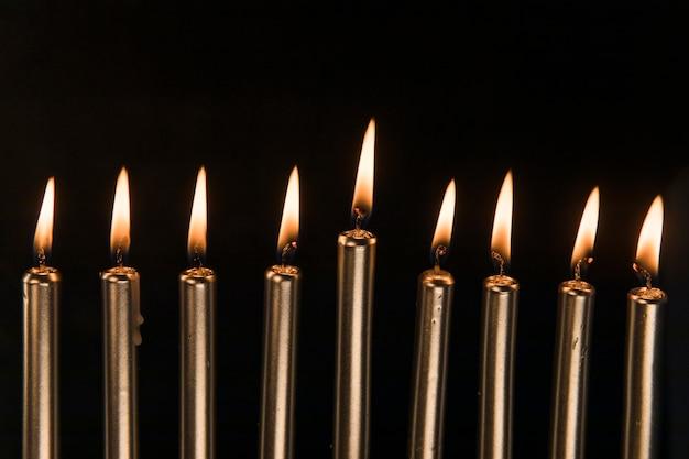 Nueve velas doradas con llama pequeña.