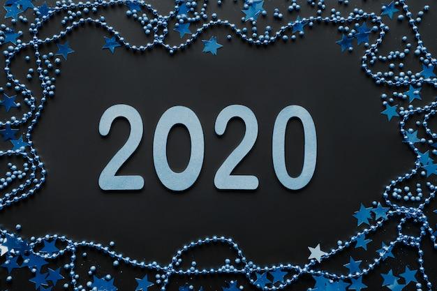 Nuevo año 2020 en color clásico azul. borde de decoración azul, brillo estrellas y perlas sobre fondo negro. feliz año nuevo. fiesta de navidad. endecha plana. vista superior. navidad.