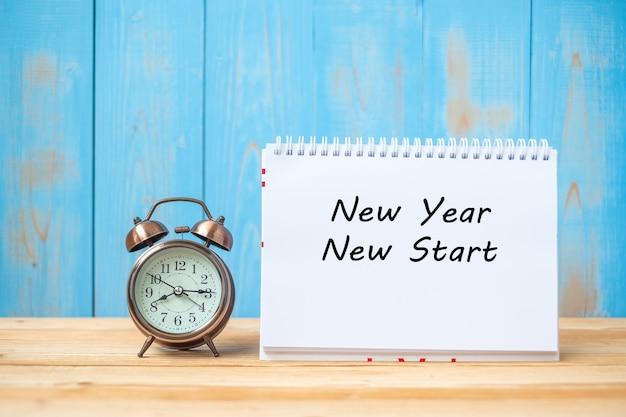 Nuevo año nuevo texto de inicio en portátil y despertador retro