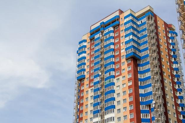 Nuevo bloque de modernos apartamentos con balcones y cielo azul.
