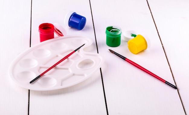 Nuevo brushe y paleta con latas de pintura sobre mesa de madera blanca