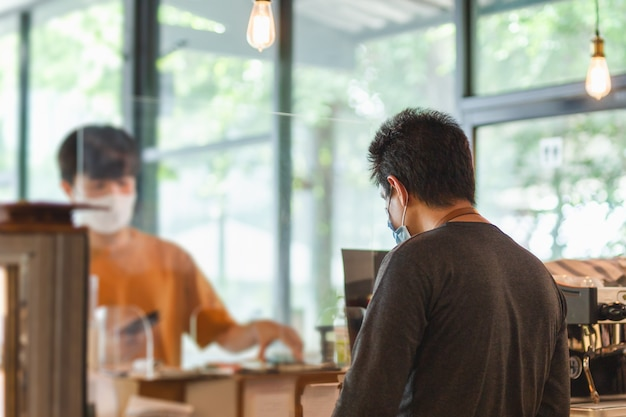 Nuevo cliente de servicio de camarero normal en el mostrador de la cafetería con protector de partición