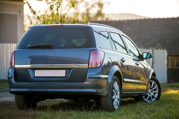 El nuevo coche gris brillante estacionó en hierba verde en fondo rural borroso del verano soleado.