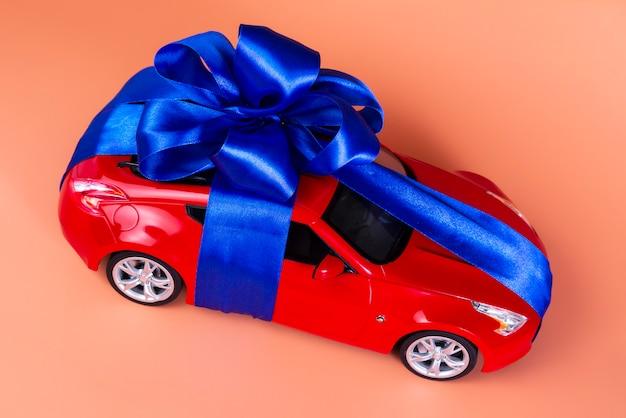 Nuevo coche rojo con un lazo azul como regalo en coral.