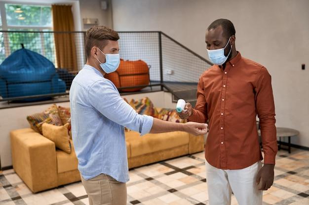 Nuevo concepto normal joven africano con máscara médica midiendo la temperatura corporal de su